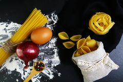 面团tagliatelle、意粉、意大利食物概念和菜单设计,在木匙子的在袋子的香料,壳,未加工的鸡蛋和面粉o 库存图片