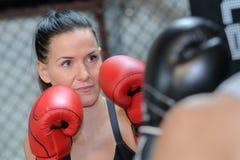 面孔严肃的女性拳击手实践的拳打 库存图片