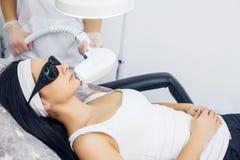 面孔关心 面部激光头发撤除 给激光Epilation治疗的美容师少妇` s面孔在秀丽诊所 身体加州 免版税库存照片
