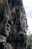 面孔在黄昏阳光下雕刻了入石头在Bayon Wat,在吴哥内的12世纪寺庙 免版税图库摄影