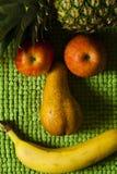 面孔果子微笑 苹果计算机、梨、菠萝和香蕉 长毛绒绿色背景 库存照片