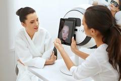 面孔皮肤分析 分析妇女脸面护理皮肤的美容师 免版税库存照片