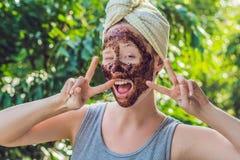 面孔皮肤洗刷 应用自然咖啡面具,面孔的性感的微笑的女性模型画象在面部皮肤洗刷 特写镜头 免版税库存图片