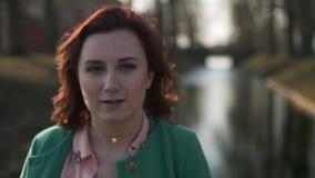 面孔-放松在宫殿零件运河附近的年轻女人的画象关闭在温暖的春天天气佩带的绿色期间 股票录像