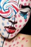 面对与一个棒棒糖的艺术在面孔 免版税库存照片