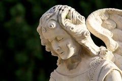 面对与看得下来的一个美好的表示的天使雕塑 免版税库存照片