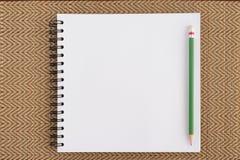 面对写生簿和铅笔在织法木头背景和文本的 库存图片