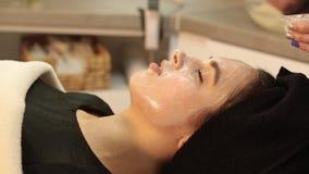 面对削皮面具,温泉秀丽治疗, skincare 可及面部关心的妇女由美容师温泉沙龙 股票视频