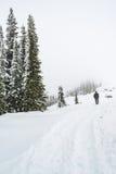面对在道路盖子的人立场山有雪的 库存照片