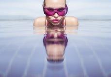 面对妇女特写镜头紫色太阳镜的在无限屋顶游泳池 免版税库存照片