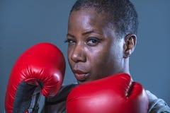 面对拳击手套的训练和摆在作为一危险figh的年轻恼怒和反抗黑人美国黑人的体育妇女画象  图库摄影