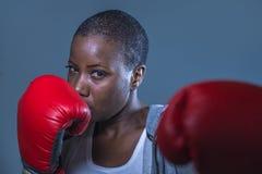 面对拳击手套的训练和摆在作为一危险figh的年轻恼怒和反抗黑人美国黑人的体育妇女画象  库存照片