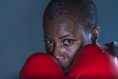 面对拳击手套的训练和摆在作为一危险figh的年轻恼怒和反抗黑人美国黑人的体育妇女画象  免版税库存照片