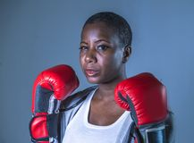 面对拳击手套的训练和摆在作为一危险figh的年轻恼怒和反抗黑人美国黑人的体育妇女画象  免版税库存图片