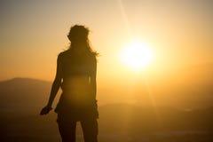 面对日落的妇女 免版税库存图片