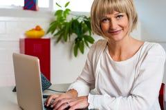 面对照相机的白肤金发的妇女,当研究膝上型计算机时 库存图片