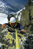 面对登山家多雪岩石的比例缩放 免版税库存照片