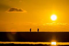 面对的人们在金黄光的海滩在日落 免版税库存图片