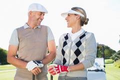 面对的愉快的打高尔夫球的夫妇与后边高尔夫球儿童车 免版税库存照片