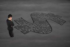 面对金钱标志迷宫的商人 免版税库存照片