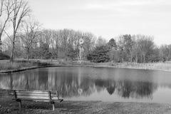 面对风车和池塘的空的公园长椅 免版税图库摄影