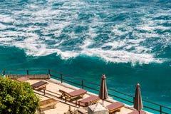 面对高地的海滩睡椅海 库存照片