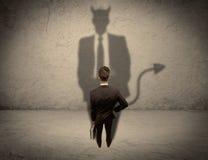 面对他自己的恶魔阴影的推销员 图库摄影