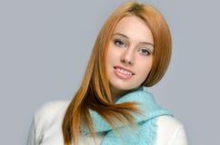 面带一蓝色围巾微笑的一名美丽的红色头发妇女的画象 免版税库存照片