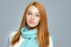 面带一蓝色围巾微笑的一名美丽的红色头发妇女的画象 库存照片