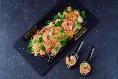 面条用大虾和菜在一块黑石板材和在传统汤匙在灰色抽象背景 免版税库存照片