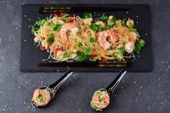 面条用大虾和菜在一块黑石板材和在传统汤匙在灰色抽象背景 图库摄影
