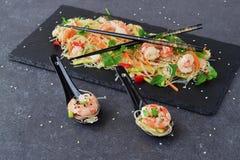 面条用大虾和菜在一块黑石板材和在传统汤匙在灰色抽象背景 库存图片