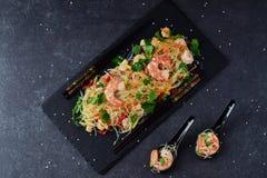 面条用大虾和菜在一块黑石板材和在传统汤匙在灰色抽象背景 库存照片