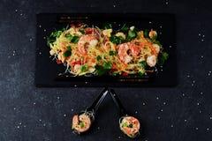 面条用大虾和菜在一块黑石板材和在传统汤匙在灰色抽象背景 免版税库存图片