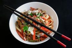 面条铁锅,有菜、草本和芝麻的 在一块白色圆的板材 在板材顶部,中国棍子是黑和红色的 库存照片
