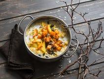 面筋免费南瓜和苹果粥 坚果牛奶燕麦粥用南瓜、苹果和蜂蜜在木棕色背景 免版税库存照片