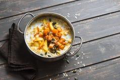 面筋免费南瓜和苹果粥 坚果牛奶燕麦粥用南瓜、苹果和蜂蜜在木棕色背景 库存图片