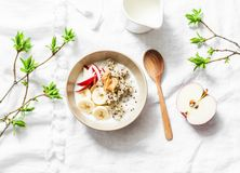 面筋免费早餐-奎奴亚藜,椰奶,香蕉,苹果,在轻的背景,顶视图的花生酱碗 可口饮食, veg 库存图片