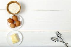 面粉、鸡蛋和黄油在一张白色桌上 免版税库存照片