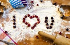 面粉、滚针、莓果和器物的心脏烘烤的在木背景 日愉快的s华伦泰 家庭爱 免版税库存照片
