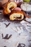 面粉的题字在桌上的,被雕刻信件用一个残破的小圆面包 免版税库存照片