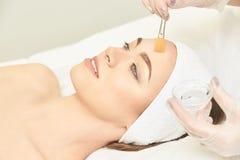 面部刷子果皮松香油治疗 剥做法的秀丽妇女 整容术少女疗法 E 库存照片