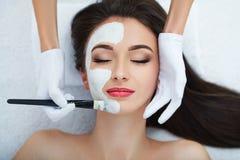 面部护肤 得到在沙龙的美丽的妇女化妆面具 免版税库存图片