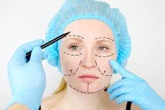 面部整容或改造,改造,面孔更正 一位整形外科医生在整容前审查一名患者 免版税图库摄影