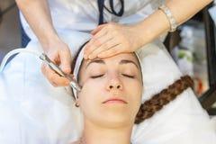 面部皮肤氧化物介质的少妇 美容师与面孔一起使用使用特别医疗设备 免版税库存图片