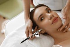 面部秀丽治疗 得到氧气皮肤削皮的妇女 免版税库存图片