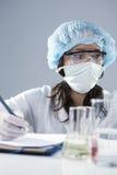 面部面具的女性实验员和在科学实验期间的防护手套 库存图片