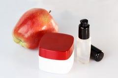 面霜,身体化妆水,奶油色瓶子,有红色盖帽的,在面霜,有液体的一个瓶附近的红色苹果奶油色瓶子身体的, f 免版税库存图片