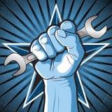 革命猛击的拳头和扳手标志 库存照片