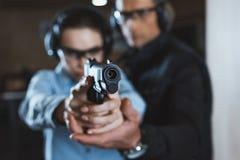 靶场的辅导员帮助的顾客与枪 免版税库存照片